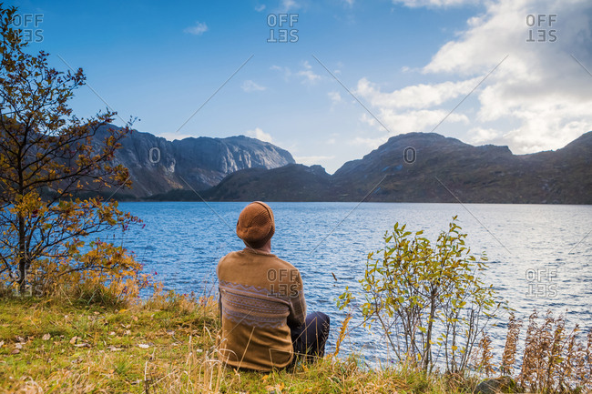 Norway- Lofoten Islands- Storvand- man sitting at the seashore