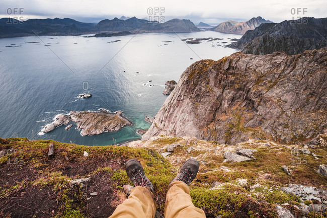 Norway- Lofoten Islands- Henningsvaer- hiker sitting on viewing point