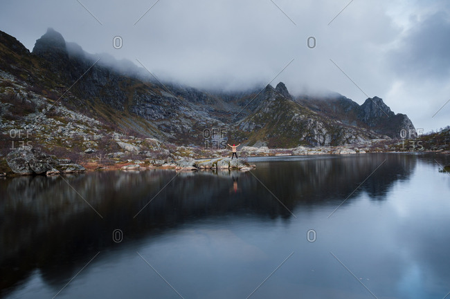 Norway- Lofoten Islands- Henningsvaer- man standing at seashore with raised arms