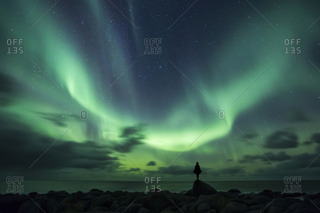 Norway- Lofoten Islands- Eggum- man standing on rock and watching northern lights