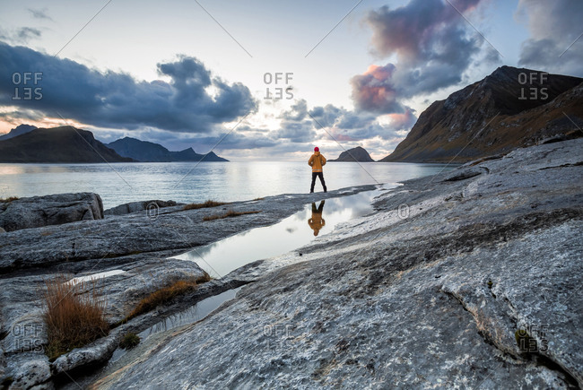 Norway- Lofoten Islands- Haukland Beach- hiker standing on rock