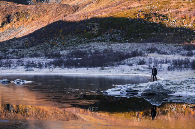 Norway- Lofoten Islands- man standing at water's edge in winter landscape