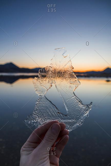 Norway- Lofoten Islands- man's hand holding thin ice