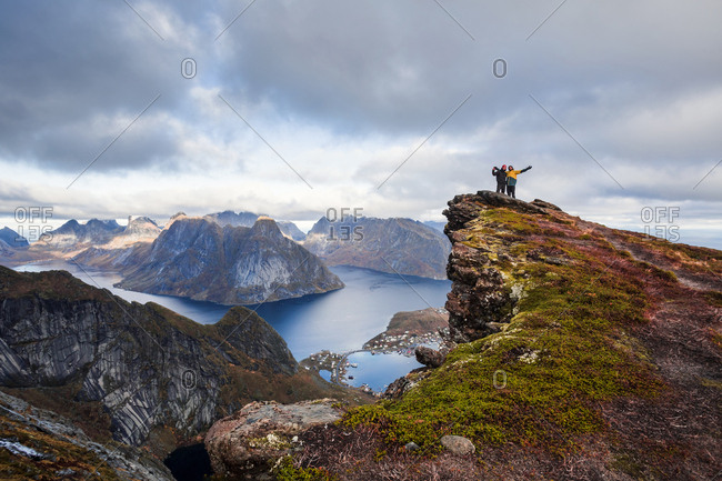 Norway- Lofoten Islands- Reine- men with raised arms standing on Reinebringen
