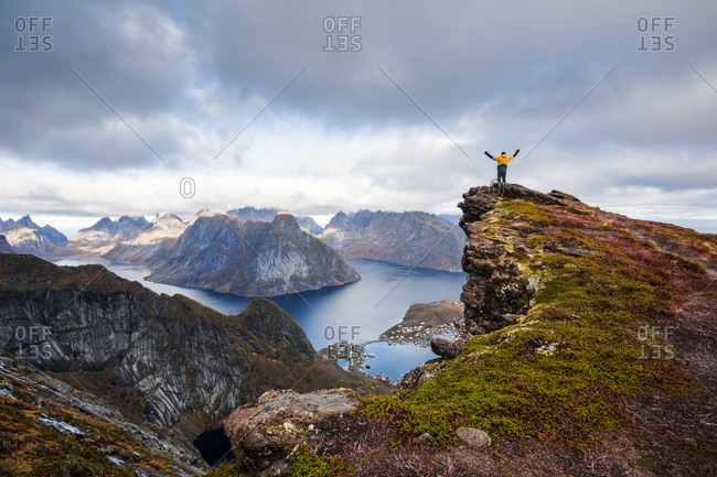 Norway- Lofoten Islands- Reine- Man with raised arms on Reinebringen