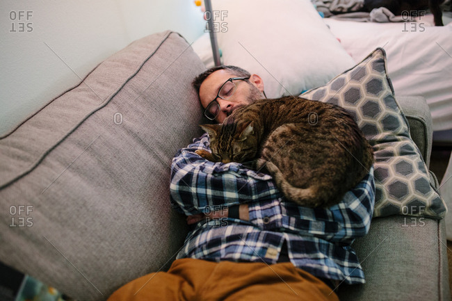 Man sleeps on couch with tabby cat sleeping on his chest
