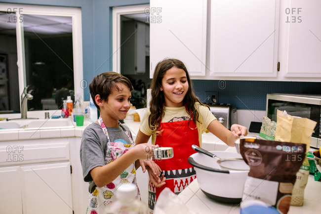 Brother and sister smile while baking in the kitchen at night