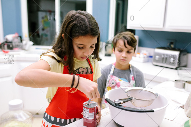 Girl measures baking soda while boy watches
