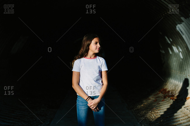 Tween girl stands in tunnel in direct light