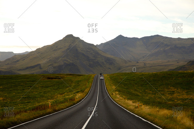 Cars driving in distance on country road in Iceland