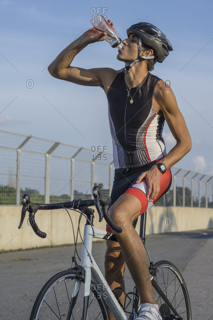 Male cyclist drinking water while training for triathlon