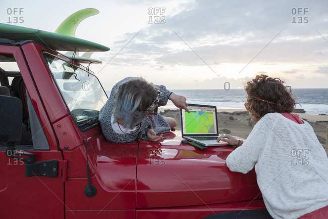 Two surfer girls  on their 4x4 car checking surf forecast on a laptop