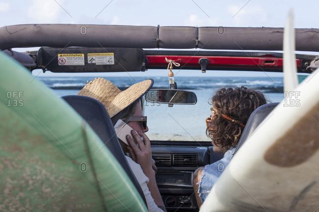 Two girls inside car with surfboards talking to the phone