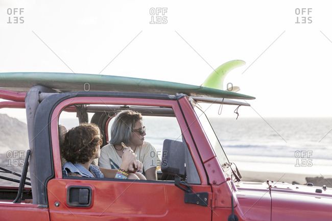 Two surfer girls with sunglasses on their 4x4 car surfboards on top