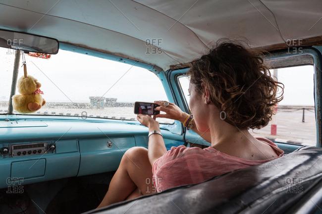 Western girl alone taking a selfie in an old vintage car in Cuba