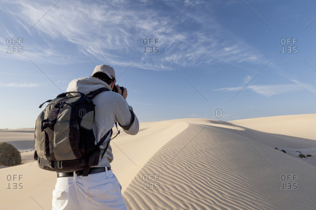 20-30 years old photographer taking photo of sand dunes of Fuerteventura