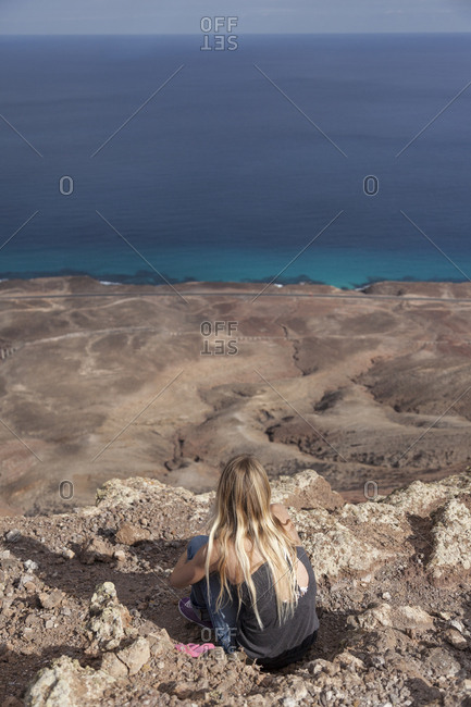 20-30 years old blonde girl admiring panorama from summit of a volcano
