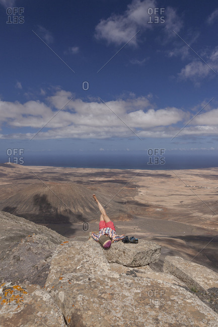 20-30 years old girl relaxing on summit of a mountain in Fuerteventura