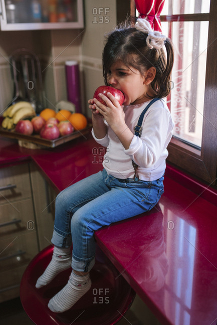Toddler girl eating a fruit on a kitchen countertop