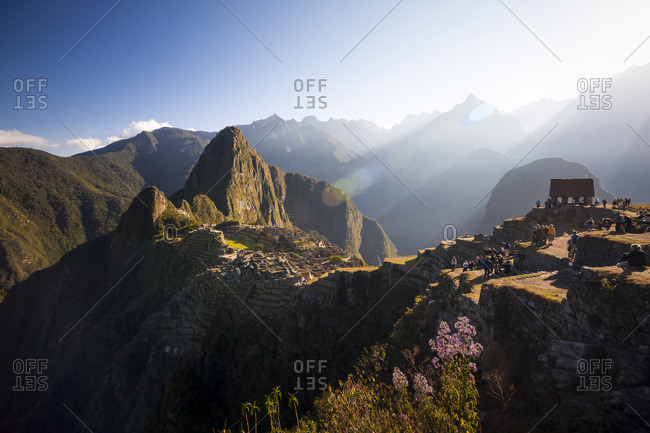 Tourists and sunrise at the ancient Inca site of Machu PIcchu,  Peru.