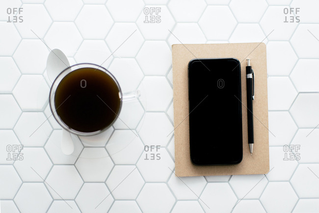 Flatlay - notebook,  coffee,  pen on white hexagon tile
