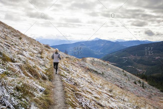 Blonde teen trail running in frozen alpine meadow