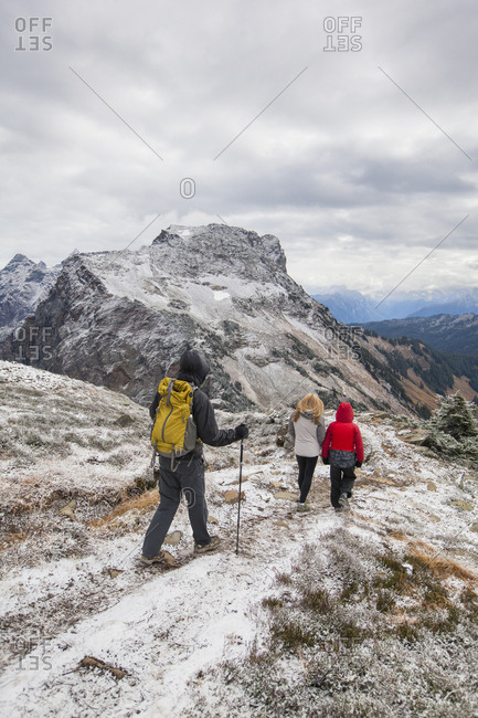 Father hiking with his two kids on a cold day