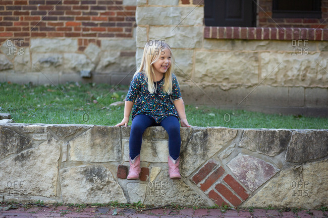 Girl sitting on fence laughing with cowboy boots on