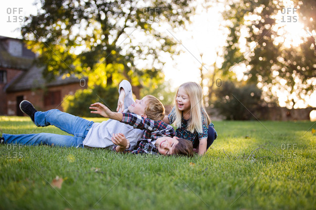 Siblings laughing and roughhousing outside in grassy field