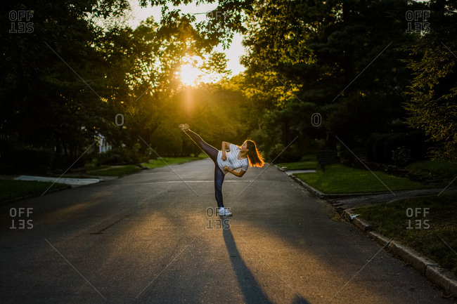A teenage girl performs martial arts kick on street at sunset