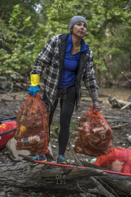 Toledo, Ohio, USA - September 23, 2018 - A woman volunteer picks up trash in the Ottawa River