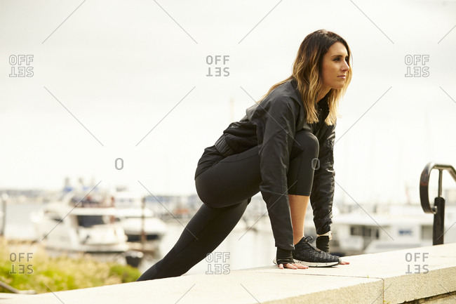 An athletic woman stretching near Boston harbor.
