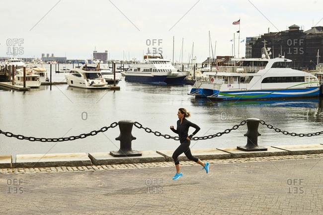 A woman runs alongside Boston harbor.