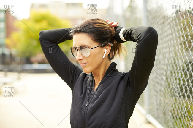 An athletic woman pulling her hair back.