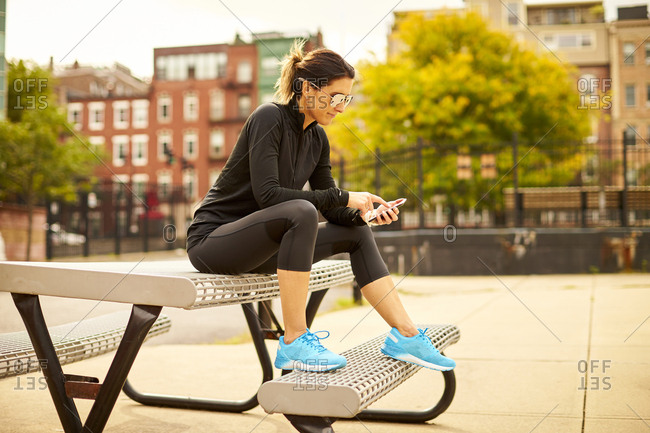 An athletic woman texting while sitting on a picnic table in a park.
