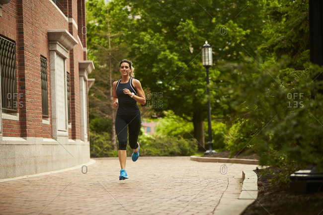 An athletic woman runs along a brick path in Boston.