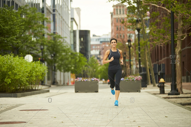 A woman running on the streets of Boston.