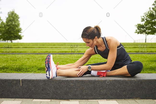 A female runner stretching near a city park in Boston.