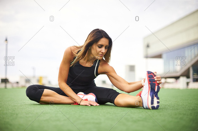 An athletic woman stretching on turf.
