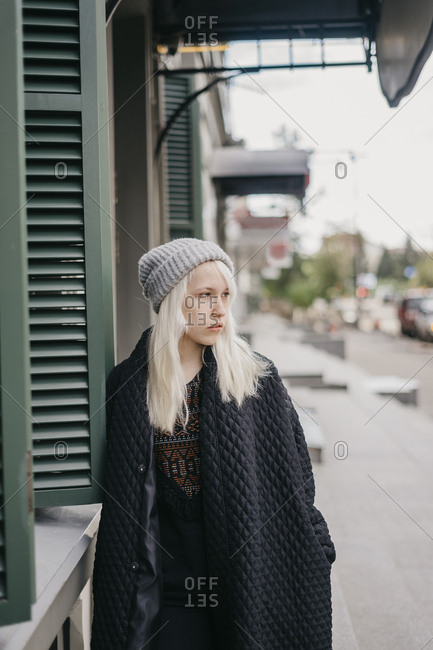 Young beautiful blonde girl standing on the street looking