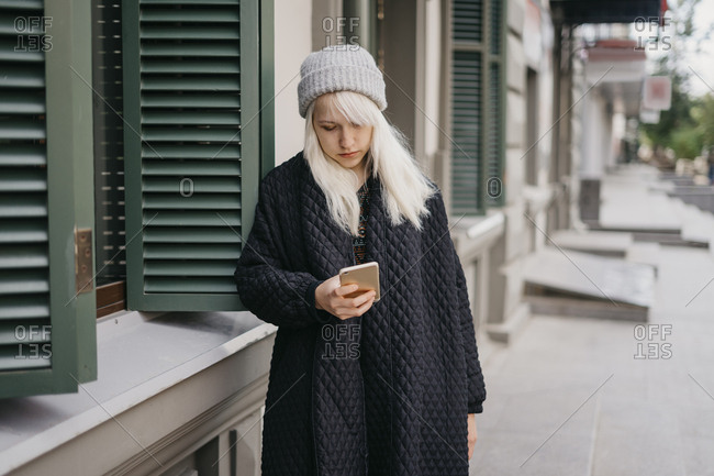 Young beautiful blonde girl standing on the street sends a text