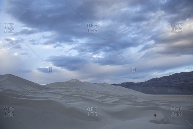 Woman standing in an immense sand dune area in the desert