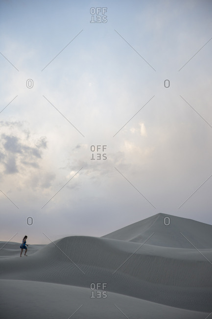 Adult woman walking on sand dunes