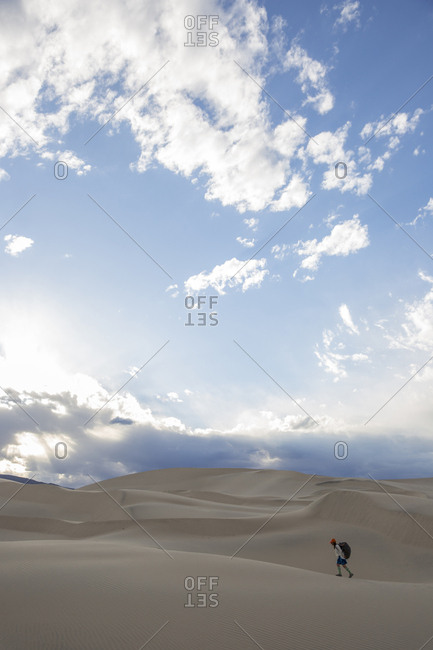 Woman walking with a heavy pack across sand dunes in the desert