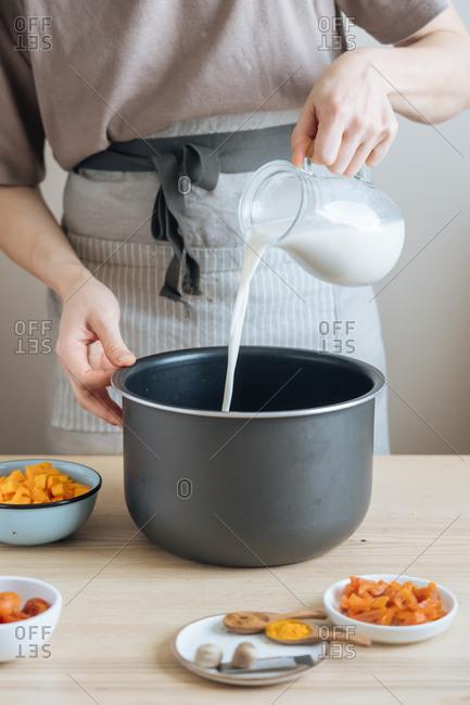 Person pouring milk into saucepan