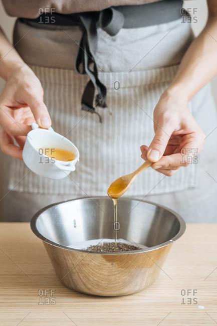 Person adding honey to bowl