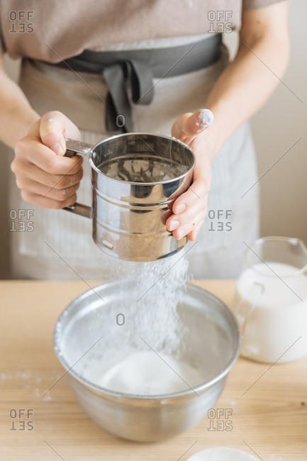 Chef sifting baking soda into a bowl