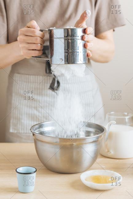 Person sifting baking soda into a bowl