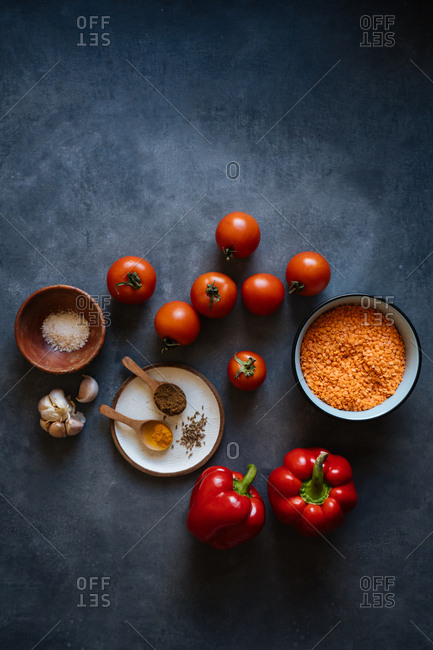 Orange lentils, red peppers and tomatoes with seasonings on dark background