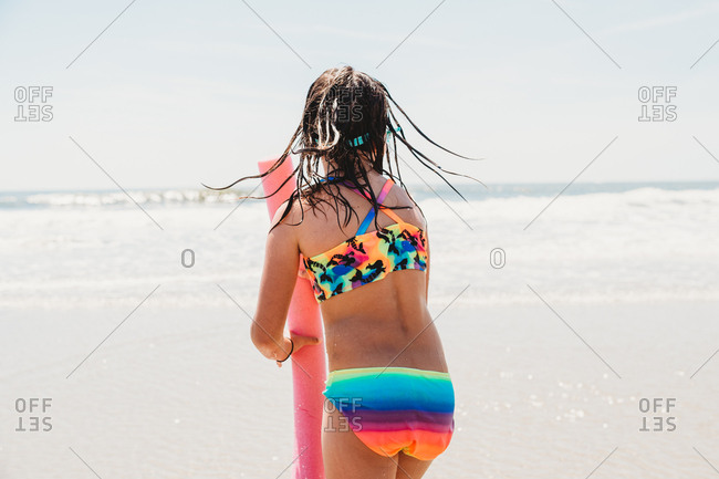 Girl wearing colorful bathing suit playing with noodle at beach